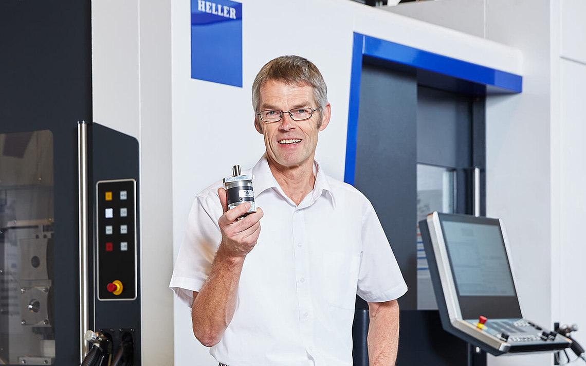 Ein Ingenieur hält ein Getriebe und gibt seine Meinung zu diesen vor der Maschine.