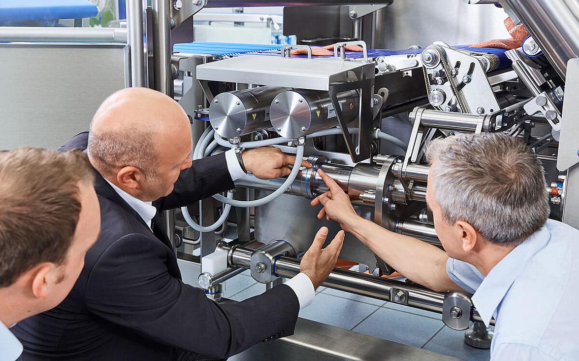 Dipendente della Neugart che dimostra ai clienti come lavora il riduttore dentro la affettatrice.