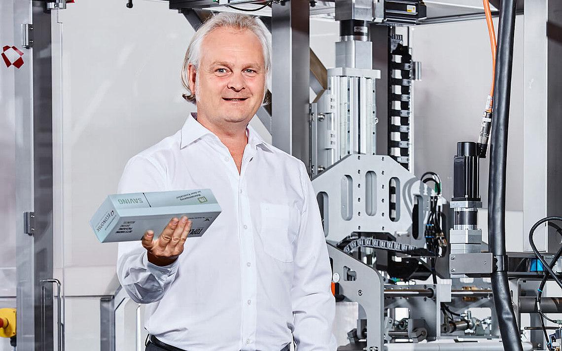 Ein Ingenieur hält ein Paket und gibt seine Meinung zu den Produkten vor der Maschine.