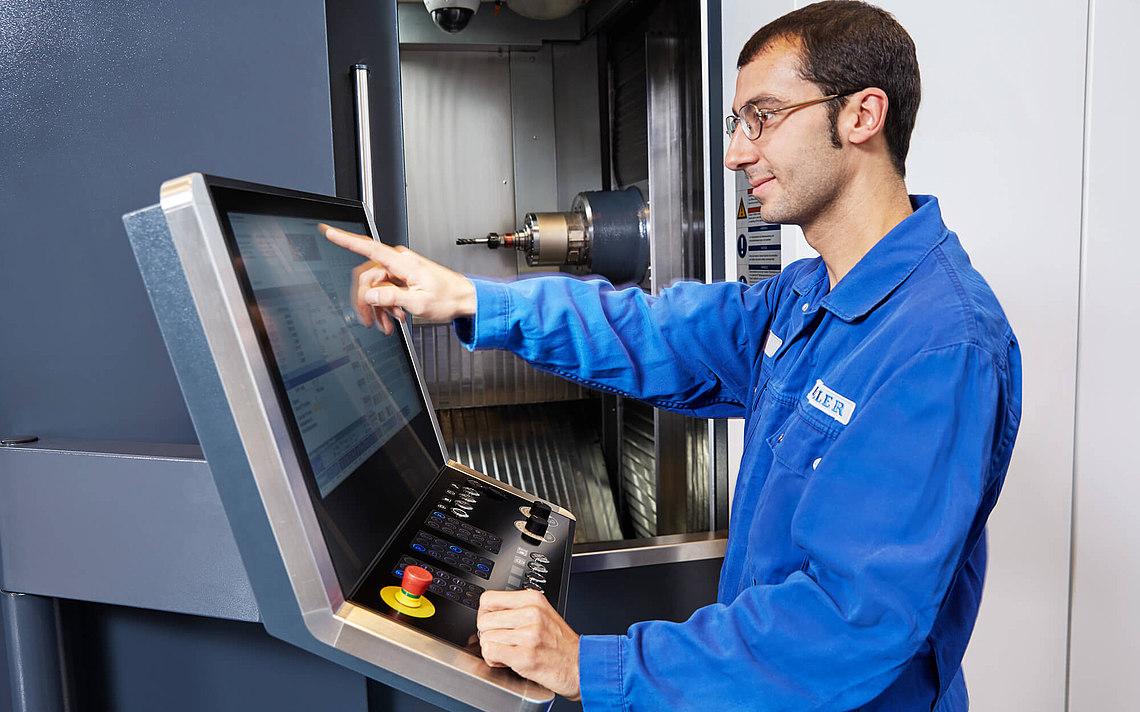 Ein Heller Angestellter arbeitet an der Werkzeugmaschine.